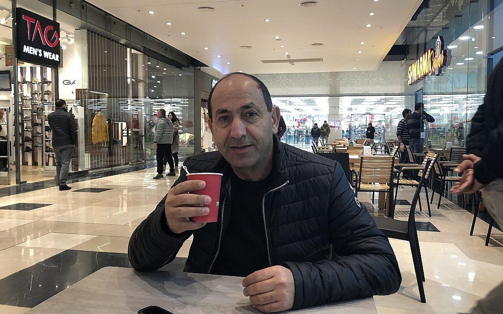 شهير فروع السوبر ماركت رامي ليفي يشرب القهوة في مجمع عتاروت، مجمعه الجديد على خط التماس بين القدس العربية واليهودية. (Jessica Steinberg/Times of Israel)
