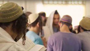 طلاب كلية 'بري هآرتس' الدينية خلال الصلاة داخل اليشيفا في مستوطنة ريحليم (Screen capture/YouTube)