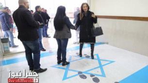 وزيرة الشؤون الإعلامية الأردنية، جمانة غنيمات (يمين) ، تطأ على العلم الإسرائيلي عند مدخل مقر نقابة عمالية في عمان، كانون الأول / ديسمبر 2018. (Screen capture: Jamuna TV)