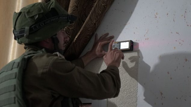 جندي اسرائيلي يقوم بمسح منزل معتدي فلسطيني قتل رجلا اسرائيليا طعنا تجهيزا لهدم المبنى في قرية يطى بالضفة الغربية، بالقرب من الخليل، 17 سبتمبر 2018 (Israel Defense Forces)