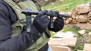 جنود يصادرون أسلحة يُزعم أنها استُخدمت في هجوم إطلاق نار على مستوطنة ميغدال عوز في الضفة الغربية من قرية فلسطينية مجاورة، في يناير 2019. (Israel Defense Forces)