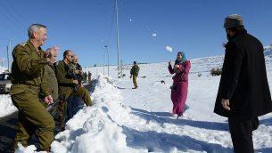 يتحدث بيني غانتس، رئيس أركان الجيش الإسرائيلي آنذاك، مع عائلة فلسطينية على طول الطريق السريع 60 في الضفة الغربية في 15 ديسمبر 2013. (Judah Ari Gross / الجيش الإسرائيلي)