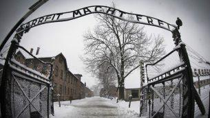 مدخل معسكر الابادة النازي 'اوشفيتس بيركيناو'، مع عبارة 'العمل يحرر' (Joel Saget/AFP)
