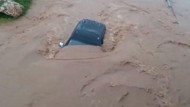 سيارة سحبتها فيضانات في نهر حيلازون في الجليل، 14 يناير 2019 (Northern District Fire and Rescue Services)