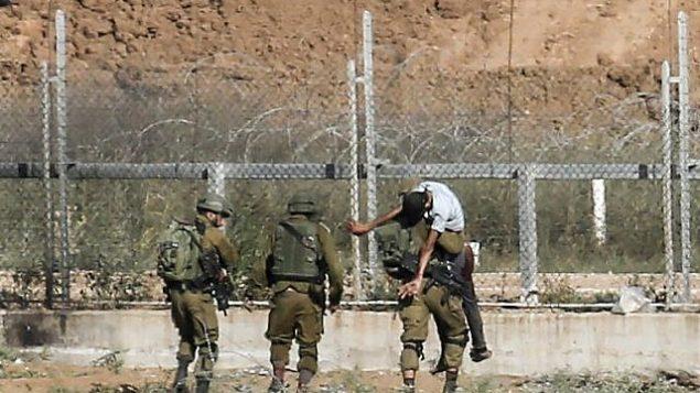 توضيحية: جنود إسرائيليون يحملون مصابا فلسطينيا يقول الجيش إنه حاول اختراق السياج الحدودي شرقي جباليا في شمال قطاع غزة، 27 يونيو، 2018. (Said Khatib/AFP)