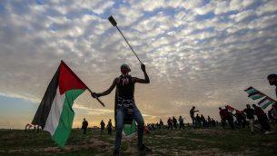 متظاهر فلسطيني يحمل العلم الوطني ومقلاع خلال مظاهرات بالقرب من السياج عند الحدود مع اسرائيل، شرقي مدينة غزة، 1 فبراير 2019 (Said Khatib/AFP)
