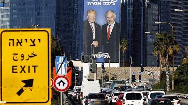 """صورة تم التقاطها في 3 فبراير، 2019 في تل أبيب يظهر فيه لوحة إعلانية ضخمة لرئيس الوزراء بينيامين نتنياهو والرئيس الأمريكي دونالد ترامب، وكُتب عليها """"نتنياهو، في مستوى آخر"""". (Jack Guez/AFP)"""