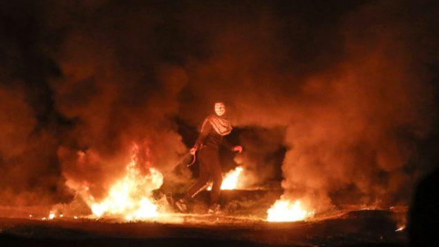 متظاهر فلسطيني مقنع يسحب إطار مشتعل خلال مظاهرات ليلية بالقرب من السياج عند الحدود مع اسرائيل، شرقي مدينة غزة، 11 فبراير 2019 (MAHMUD HAMS / AFP)