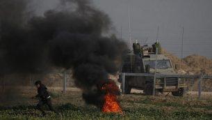 أحد المتظاهرين الفلسطينيين يركض بالقرب من الإطارات المحترقة خلال مظاهرة بالقرب من السياج على طول الحدود مع إسرائيل، شرق مدينة غزة، في 15 فبراير، 2019. تظهر سيارة عسكرية إسرائيلية على الجانب الآخر من السياج. (Said Khatib/AFP)