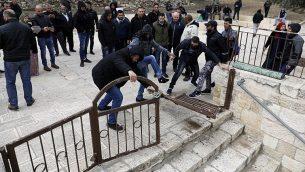 متظاهرون فلسطينيون يكسرون بوابة مغلقة في الحرم القدسي، 18 فبراير 2019 (Ahmad Gharabli/AFP)