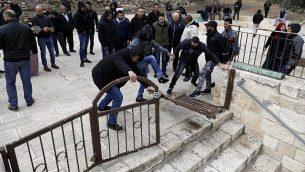 متظاهرون فلسطينيون يقومون بتحطيم وفتح بوابة مغلقة في المسجد الأقصى في القدس القديمة، 18 فبراير، 2019. (Ahmad Gharabli/AFP).