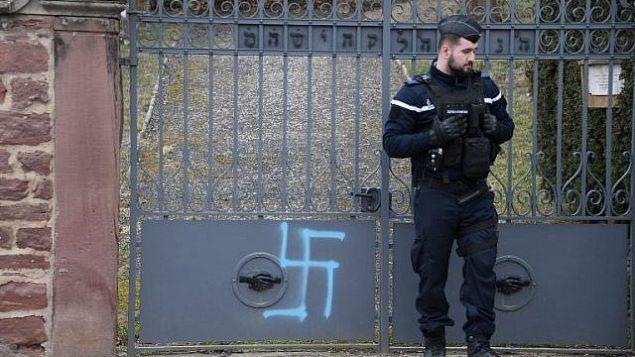 رجل شرطة في بلدة كواتينهيم الفرنسية يقف أمام مدخل مقبرة يهودية تم تدنيس قبورها في 19 فبراير، 2019. (Frederick FLORIN / AFP)