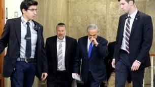 رئيس الوزراء بنيامين نتنياهو يصل مع سكرتير الحكومة في ذلك الوقت، أفيحاي ماندلبلي ، الثاني من اليسار، لحضور اجتماع وزاري في مكتب نتنياهو في القدس في 20 كانون الأول / ديسمبر 2015. (AFP/Pool/Gali Tibbon)
