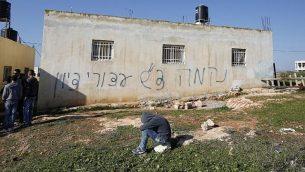 فلسطينيون يحتشدون بالقرب من منزل خط عليه عبارات 'انتقام' و'تحية من أسرى صهيون'، في قرية بيت إللو في الضفة الغربية، 22 ديسمبر، 2015. (AFP PHOTO/ABBAS MOMANI)