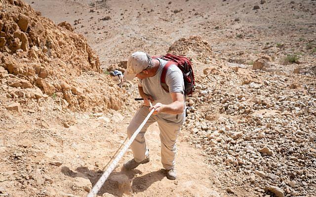 الباحث أورين غوتفيلد ينحدر من الكهف 52، في موقع قمران الأثري، 22 يناير، 2019. (Luke Tress / Times of Israel)