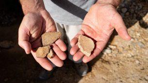 شظايا قديمة خارج كهف في قمران، فوق البحر الميت. يعود تاريخ القطع على اليسار إلى ما يقارب 2000 سنة، والقشرة الموجودة على اليمين أكبر بآلاف السنين، 22 يناير، 2019. (Luke Tress / Times of Israel)