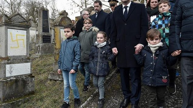 الرئيس الفرنسي إيمانويل ماكرون يمسك بأيد أطفال خلال زيارة قام بها إلى مقبرة يهودية تم تدنيسها في كواتينهيم، شرق فرنسا، 19 فبراير، 2019. (Frederick Florin, Pool via AP)