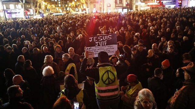 """رجل يرتدي سترة صفراء يحمل لافتة كُتب عليها """"أنا يهودي""""، خلال احتشاد في ميدان الجمهورية احتجاجا على معاداة السامية، باريس، فرنسا، 19 فبراير، 2019. (AP Photo/Thibault Camus)"""