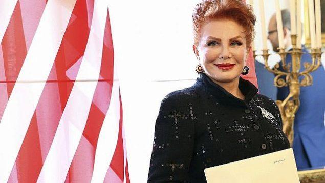 في هذه الصورة من يوم 6 سبتمبر، 2016، تقف جورجيت موسباكر إلى جانب العلم الأمريكي بعد حصولها على أوراق اعتمادها كسفيرة للولايات المتحدة لدى بولندا في وارسو. (AP Photo/Czarek Sokolowski, File)