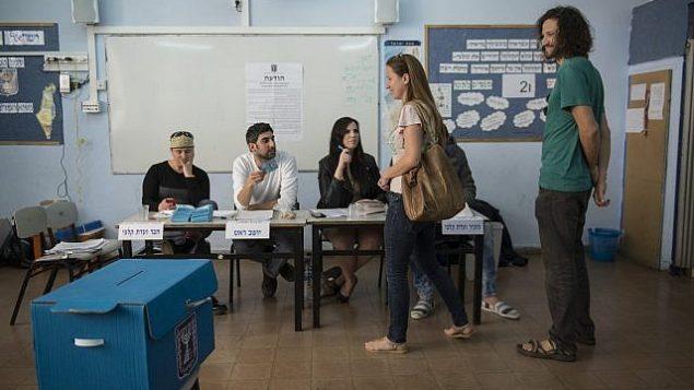 إسرائيليون يقفون في الصف للإدلاء بأصواتهم في محطة اقتراع في تل أبيب، للكنيست ال20، في الانتخابات العامة الإسرائيلية، 17 مارس، 2015.  (Danielle Shitrit/FLASH90)