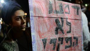 امرأة اسرائيلية ترفع لافتة مكتوب عليها 'دمائنا ليس رخيصة' خلال مظاهرة في تل ابيب في اعقاب قتل اوري انسباخر، 9 فبراير 2019 (Tomer Neuberg/Flash90)