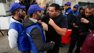 مستوطن اسرائيلي يتشاجر مع اعضاء مجموعة مراقبين فلسطينيين جديدة في مدينة الخليل بالضفة الغربية، 10 فبراير 2019 (Wisam Hashlamoun/Flash90)