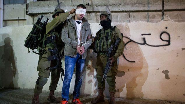 صورة توضيحية لجنود إسرائيليين يقومون بتعصيب أعين معتقلين فلسطينيين، 8 ديسمبر 2015 (Nati Shohat/Flash90.)