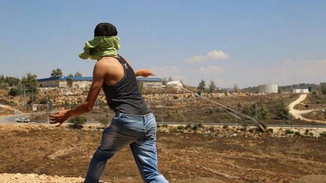 توضيحية: فلسطيني من قرية النبي صالح في الضفة الغربية يلقي بحجر على الجنود الإسرائيليين. (Eric Cortellessa/Times of Israel)