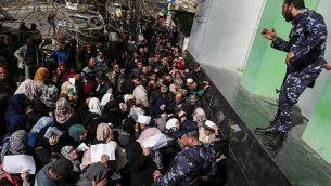 قوى الأمن الفلسطينية الموالية لحركة حماس تنظم الصف خارج مكتب البريد المركزي في مدينة غاز في 26 يناير، 2019، مع احتشاد الفلسطينيين للحصول على مساعدة مالية من قطر.  (Mahmud Hams/AFP)