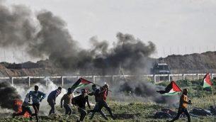 فلسطينيون يحملون الأعلام الفلسطينية يمرون من أمام إطارات محترقة خلال مواجهات بالقرب من السياج الحدودي مع إسرائيل، شرق مدينة غزة، 22 فبراير، 2019. (Mahmud Hams/AFP)