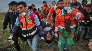 مسعفون فلسطينيوم ينقلون شابا مصابا خلال مواجهات في اعقاب مظاهرة عند الحدود مع إسرائيل شرق مدينة غزة، 1 مارس، 2019.  (SAID KHATIB / AFP)
