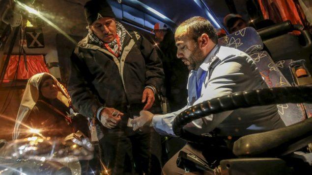 شرطي تابع لحركة حماس يفحص وثائق سفر معتمرين فلسطينيين يصعدون على متن حافلة في معبر رفح بين قطاع غزة ومصر، 3 مارس 2019 (SAID KHATIB / AFP)