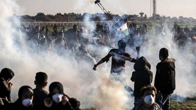 فلسطيني يستخدم مقلاعا لقذف عبوة الغاز المسيل للدموع التي ألقتها القوات الإسرائيلية خلال اشتباكات على السياج على طول الحدود مع إسرائيل، شرق مدينة غزة، في 8 مارس / آذار 2019. (Mahmud Hams/AFP)
