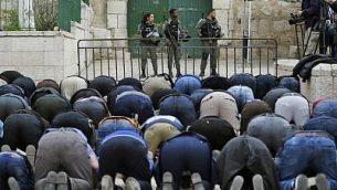 مصلون مسلمون فلسطينيون يصلون أمام حاجز بعد أن قامت شرطة حرس الحدود الإسرائيلية بإغلاق أحد مداخل الحرم القدسي في البلدة القديمة، 12 مارس، 2019. (Ahmad GHARABLI / AFP)