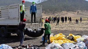 تحميل الحطام على شاحنة في موقع تحطم طائرة بوينغ 737 MAX التي تديرها الخطوط الجوية الإثيوبية، في قرية حماة قنشوشيل في منطقة أوروميا، في 13 مارس 2019. (TONY KARUMBA / AFP)