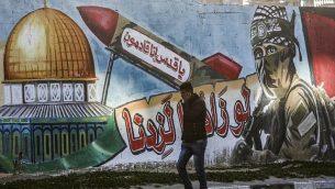 """رجل فلسطيني يمر من أمام رسم لمقاتل ملثم من كتائب القسام، الجناح العسكري لحركة حماس، وإلى جانبه صاروخ تظهر عليه عبارة """"يا قدس إنا قادمون"""" وقبة الصخرة، في أحد شوارع رفح في قطاع غزة، 14 مارس، 2019. (Photo by SAID KHATIB / AFP)"""