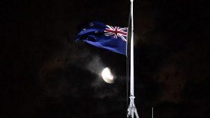 تنكيس العلم النيوزيلندي في مبنى البرلمان إلى المنتصف في ولنغتون في 15مارس، 2019، بعد إطلاق نار وقع في مدينة كرايست تشيرتش. الهجومان الذان وقعا في 15 مارس أسفرا عن مقتل 49 شخصا، قام خلالهما أحد المسلح، الذي ورد أنه أسترالي الجنسية، كما يبدو بنقل الهجوم في بث حي عبر الإنترنت. (Marty Melville/AFP)
