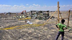 طفل يتفرج على محققي الأدلة الجنائية وهم يقومون بتمشيط الأرض بحثا عن أدلة حمض نووي بالقرب من كومة من خطاب الطائرة في موقع تحطم طائرة الخطوط الجوية الإثيوبية من طراز 'بوينغ 737 ماكس 8' ، 16 مارس، 2019، في قرية قريبة من بيشوفتو في منطقة أوروميا.  (TONY KARUMBA / AFP)