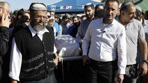 المشيعون يحملون جثمان الحاخام إحيعاد إتينغر (47 عاما)، الذي توفي متأثر بجراح أصيب بها في اليوم السابق خلال هجوم إطلاق نار وطعن، خلال جنازته في مستوطنة إيلي، 18 مارس، 2019. (MENAHEM KAHANA / AFP)