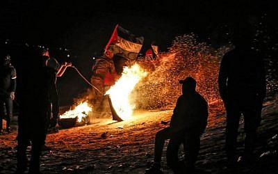 متظاهرون فلسطينيون يشاركون في مظاهرة ليلية بالقرب من السياج الحدودي مع إسرائيل، في مدينة رفح جنوب قطاع غزة، 19 مارس، 2019. (SAID KHATIB / AFP)