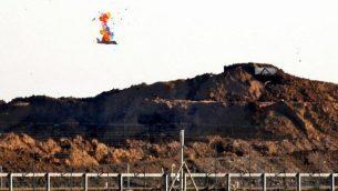 هذه الصورة تم التقاطها في 22 مارس، 2019 تظهر بالونات تحمل جسما يدوي الصنع على شكل طائرة مسيرة يحلق فوق الحدود مع إسرائيل شرق مدينة غزة، بعد إطلاقه من قبل متظاهرين فلسطينيين خلال احتجاجات عن السياج الحدودي.  (Said KHATIB / AFP)