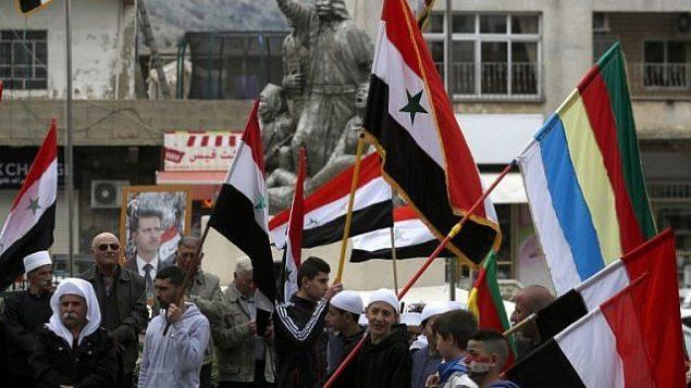 سكان هضبة الجولان يرفعون الأعلام السوري أمام صورة للرئيس السوري بشار الأسد خلال مظاهرة أقيمت احتجاجا على إعتراف الرئيس الأمريكي دونالد ترامب بالسيادة الإسرائيلية على المنطقة المتنازع عليها، في بلدة مجدل شمس، 23 مارس، 2019.  (Jalaa Marey/AFP)