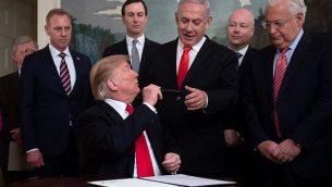 الرئيس الامريكي دونالد ترامب يقدم قلمه الى رئيس الوزراء بنيامين نتنياهو ، بعد التوقيع على اعلان يعترف بالسيادة الإسرائيلية في مرتفعات الجولان، في غرفة الاستقبال الدبلوماسية في البيت الابيض، بواشنطن، 25 مارس 2019 (SAUL LOEB/AFP)