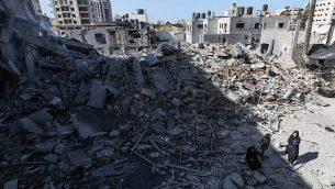 صورة تم التقاطها في 26 مارس، 2019، يظهر فيها فلسطينيون يقفون بالقرب من أنقاض أحد المباني في مدينة غزة، بعد أن استهدفت غارات جوية إسرائيلية عشرات المواقع في جميع أنحاء القطاع ليلا ردا على إطلاق صاروخ من القطاع الفلسطيني.  (MAHMUD HAMS / AFP)