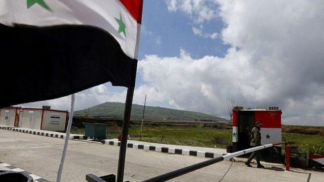 صورة توضيحية: جندي سوري بمر بالقرب من نقطة حدودية عند الحدود مع اسرائيل، في بلدة الثنيطرة السورية في مرتفعات الجولان، 26 مارس 2019 (Louai Beshara/AFP)