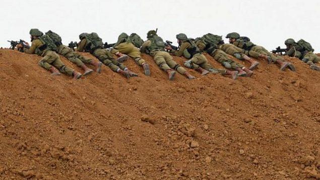 في هذه الصورة ، التي تم التقاطها في 30 مارس 2018، يحتفظ الجنود الإسرائيليون بمواقفهم على طول الحدود مع قطاع غزة في كيبوتس ناحال عوز، بينما يتظاهر الفلسطينيون في الجانب الآخر للاحتفال بيوم الأرض. Jack Guez/AFP)