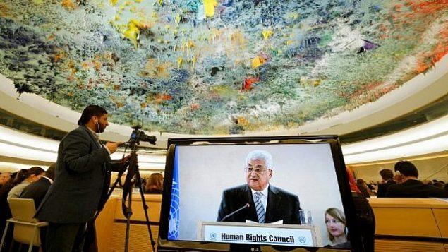 رئيس السلطة الفلسطينية محمود عباس على شاشة تلفزيون أثناء حديثه خلال اجتماع لمجلس حقوق الإنسان التابع للأمم المتحدة في 27 فبراير 2017 في جنيف، سويسرا. (AFP/Fabrice Coffrini)