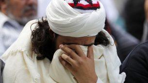 رجل مسلم يبكي خلال صلاة الجمعة في جديقة هاغلي في كرايست تشيرتش، نيوزيلندا، 22 مارس 2019 (AP Photo/Vincent Thian)