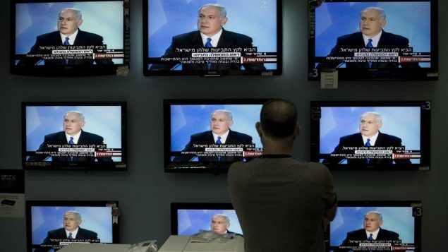 صورة توضيحية: رجل اسرائيلي يشاهد خطاب لرئيس الوزراء بنيامين نتنياهو على شاشات تلفزيون في متجر بالقدس، 14 يونيو 2009 (AP/Bernat Armangue/File)