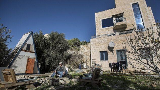 موشيه غوردون يجلس امام الشقة التي اعلن عنها في موقع 'اير بي ان بي' في مستوطنة نوفي برات في الضفة الغربية، 17 يناير 2016 (AP Photo/Tsafrir Abayov, File)